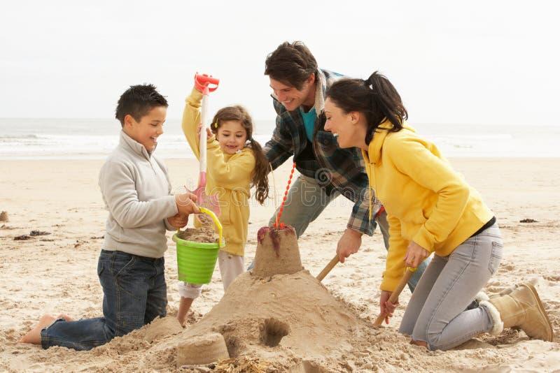 Sandcastle do edifício da família na praia do inverno fotos de stock