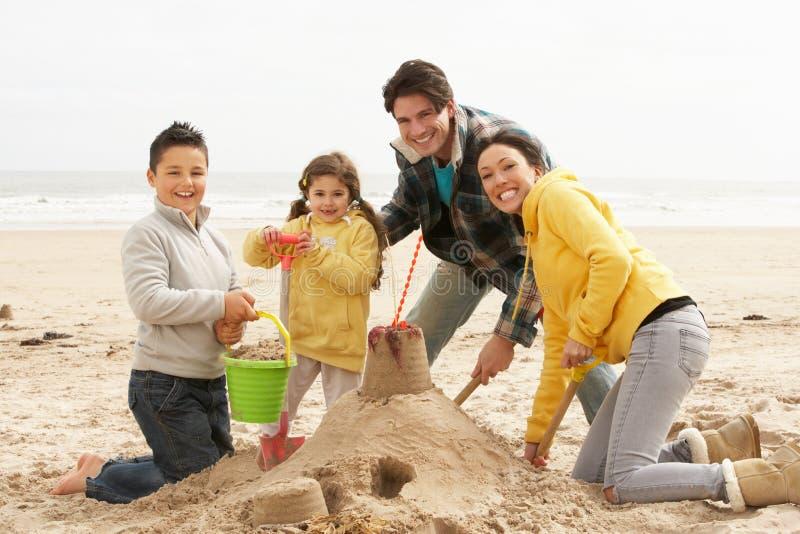 Sandcastle do edifício da família na praia do inverno fotografia de stock
