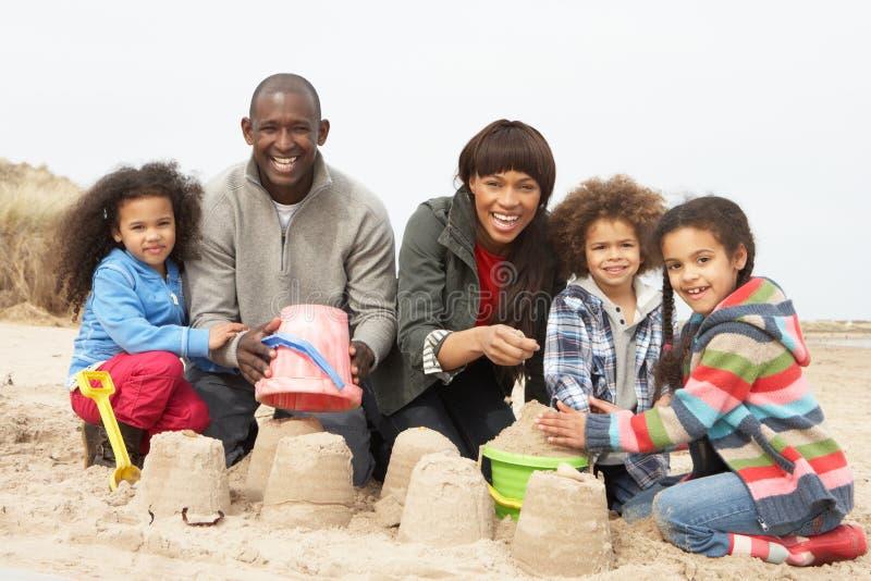 Sandcastle novo do edifício da família no feriado da praia imagem de stock royalty free