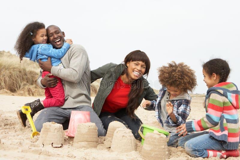 Sandcastle novo do edifício da família no feriado da praia imagens de stock