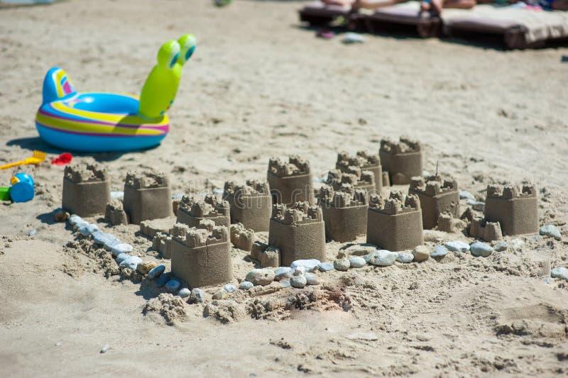A sandcastle on a sandy beach, set against a bright blue summer sky.  stock photos