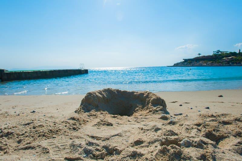 A sandcastle on a sandy beach, set against a bright blue summer sky.  stock photo