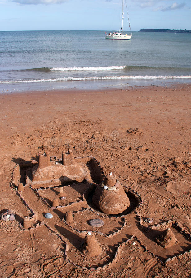 Sandcastle und Segelnboot lizenzfreie stockfotografie