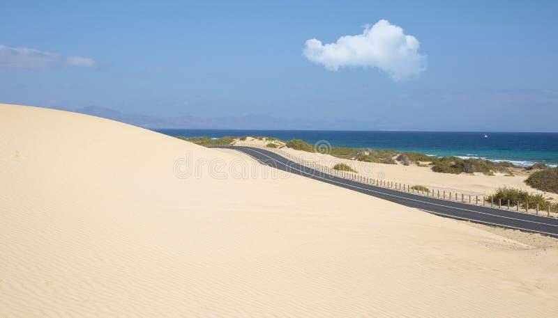 Sanddünen in Nationalpark Corralejo und in der Ansicht von Meer und von Straße, Fuerteventura stockbild