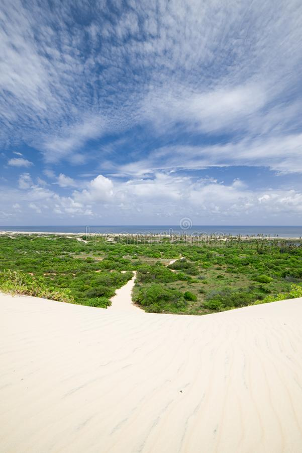 Sanddyn som leder till en väg till och med ett grönt fält och havet molnig sky fotografering för bildbyråer