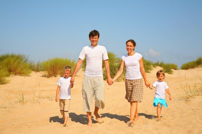 sanden för familj fyra går royaltyfria foton