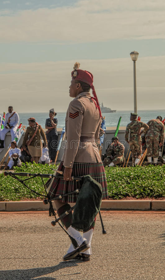 SANDF-musikbandmedlem som bär den fulla skotska regaliern och bär ett säckpipe- arkivbild