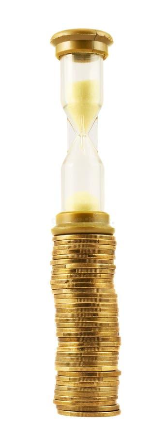 Sandglass au-dessus d'une pile de pièce de monnaie d'isolement image libre de droits