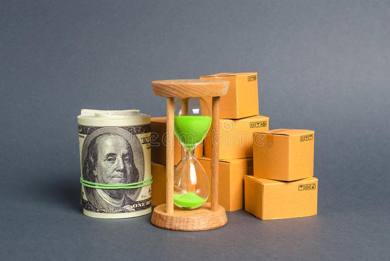 A sandglass, bundle of dollar money and cardboard boxes. Business and commerce. Production export of products and goods around royalty free stock images