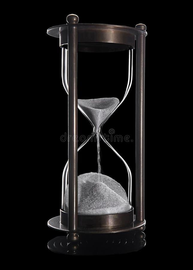 Sandglass de bronze com a areia branca isolada no preto imagens de stock royalty free