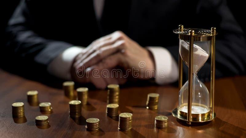 Sandglass de observação da pessoa rica, renda de espera dos projetos de investimento imagem de stock royalty free
