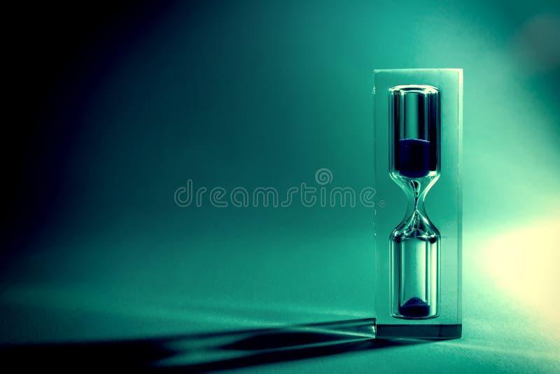 Sandglass del reloj de arena con las sombras y el resplandor del sol en un fondo oscuro Foto retra vieja del vintage del estilo fotos de archivo libres de regalías