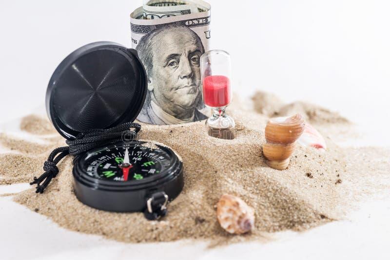 sandglass, dollar och kompass på sand som isoleras på vit royaltyfria bilder