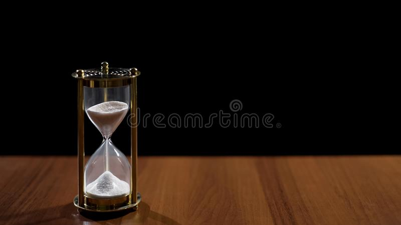 Sandglass measuring time by sand flow, life passing quickly, time management royalty free stock photography