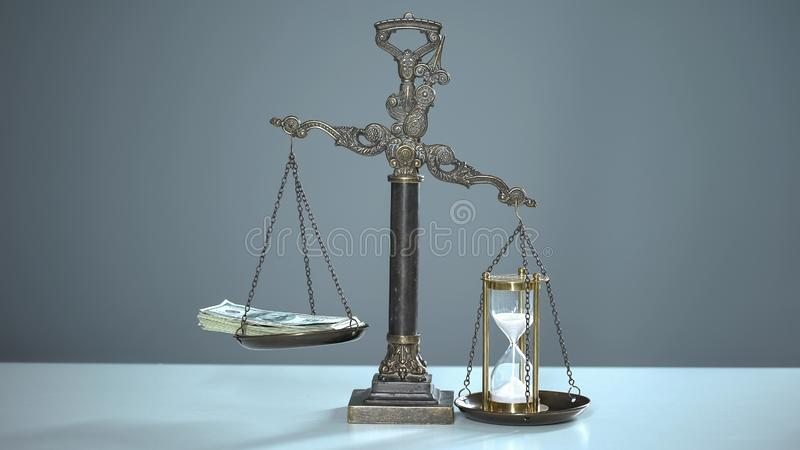 Sandglass outweighs dollars on scales, time is money, valuable resources usage royalty free stock photo