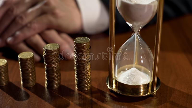 Sandglass and piles of coins on table, depositor earning interest on savings royalty free stock image