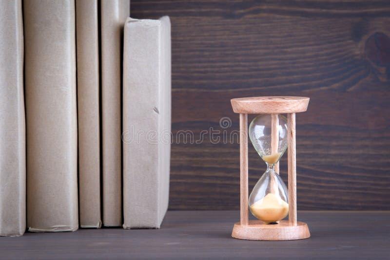 Sandglass, Sanduhr oder Eieruhr auf dem Holztisch, der heraus das letzte zweite zeigt oder letztes oder Zeit stockbilder