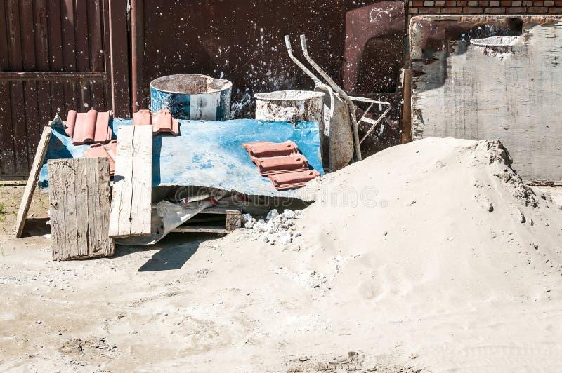 Sandhaufen mit Laufkatze und anderes Architekturmaterial und Werkzeuge vor dem Wohngebäude-Zusammenziehungsstandort auf stockbilder