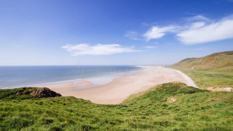 Sandig strand för Rhossili fjärd på en solig molnig gräsplan för dagsommartid royaltyfri bild
