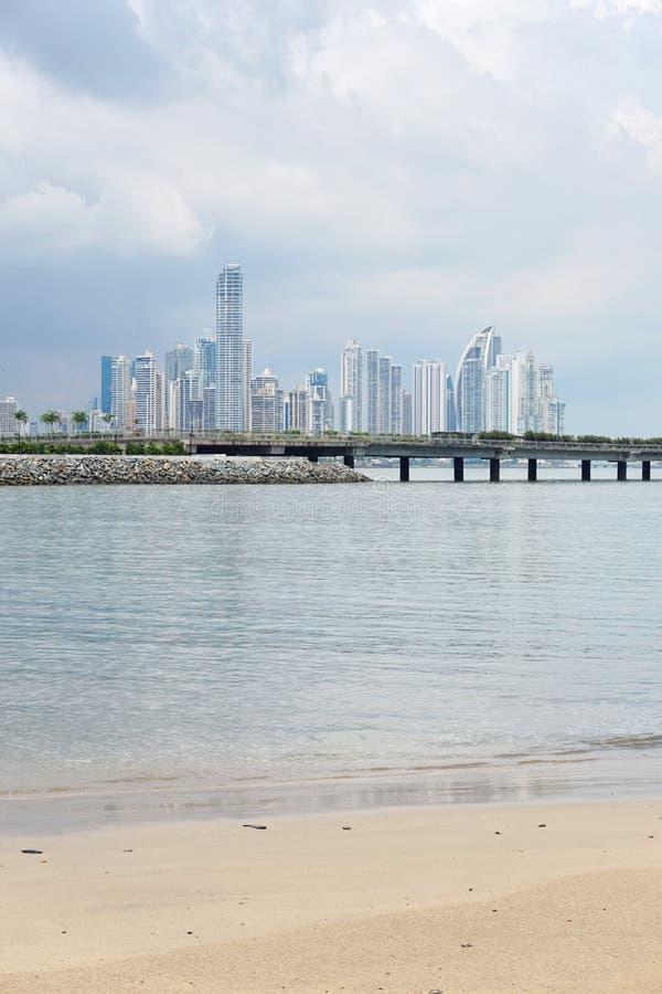 Sandig strand med skyskrapor av Panama City arkivfoto
