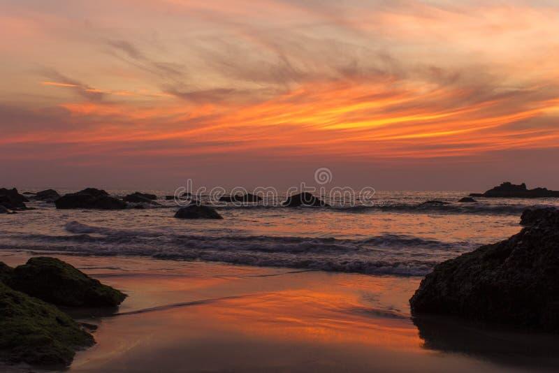 Sandig strand med stora stenar mot bakgrunden av havsvågor under en ljus orange purpurfärgad solnedgånghimmel royaltyfria bilder