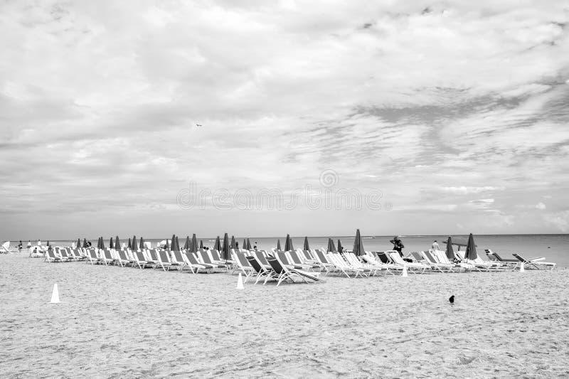 Sandig strand med sunbeds och vikta rosa paraplyer arkivfoto