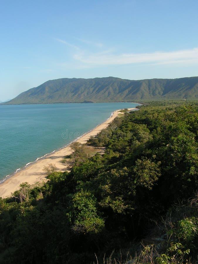 Sandig strand och blått vatten royaltyfri bild