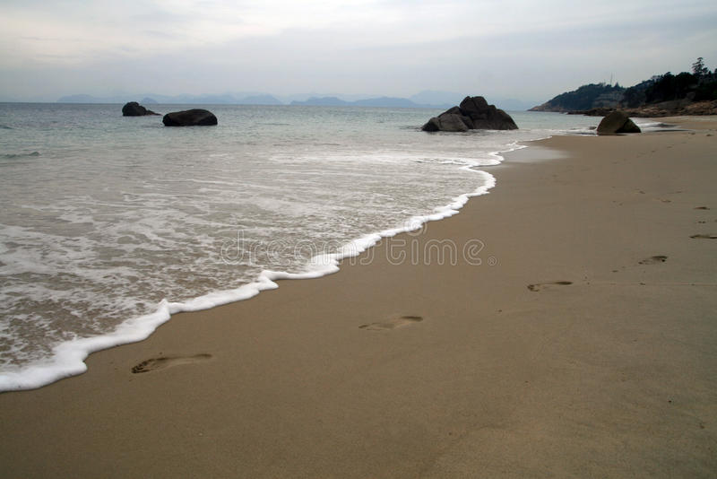 sandiga strandfotspår royaltyfria bilder