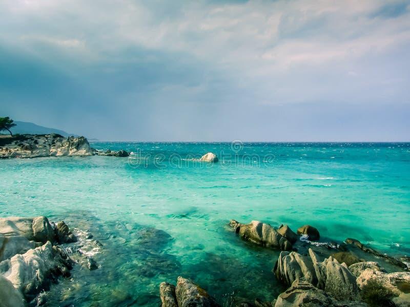 sandiger Strand mit Abdr?cken im Sand, im blauen gewellten Meer und im bew?lkten Himmel in der D?mmerung lizenzfreie stockfotos