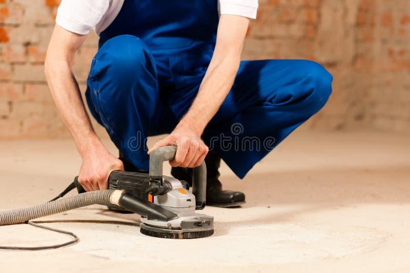 Sanding the cement floor. Construction worker working grinding the cement floor royalty free stock photo