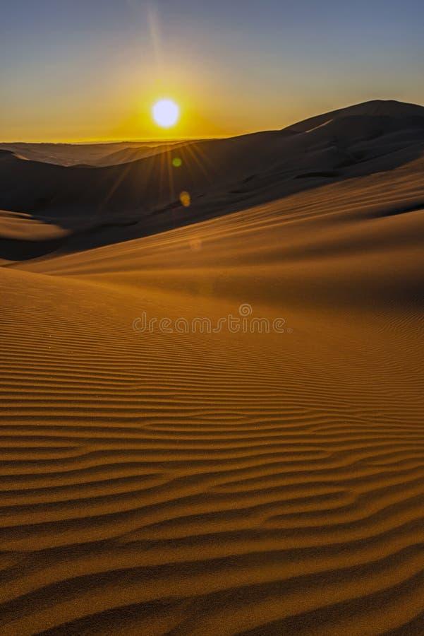 Sandkrusningar på solnedgången i öknen, Peru arkivfoto