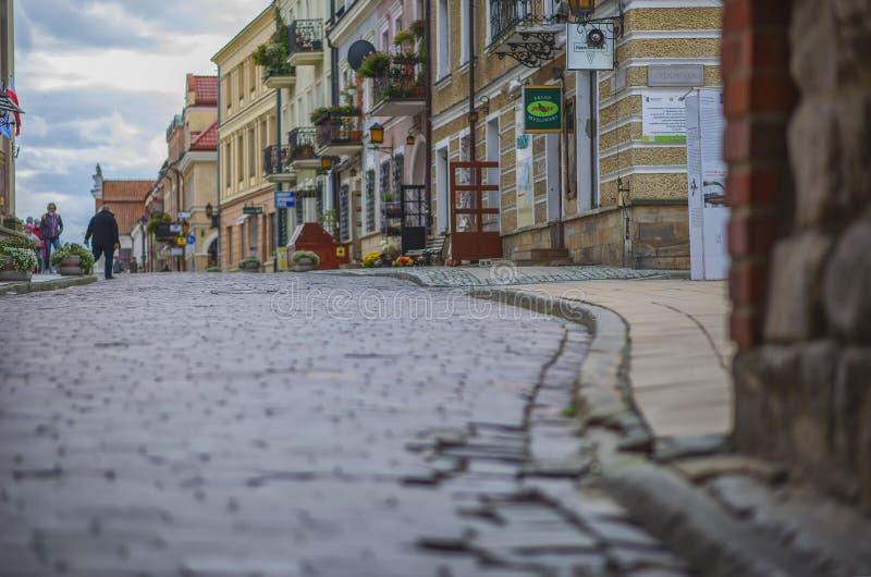 Sandomierz kullerstengata i staden Polen arkivfoton