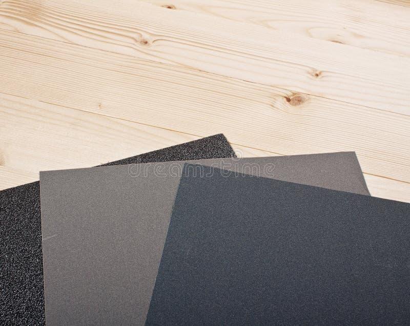Sandpapper på träplankor arkivbild