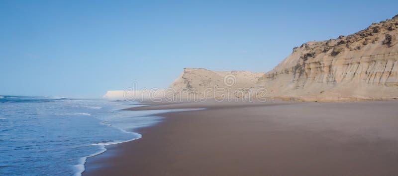 Sandpappra klippor av Dakhla i den Västsahara regionen av Marocko, med havet arkivbilder
