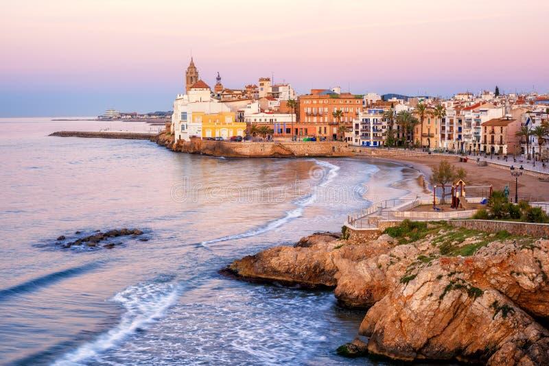 Sandpappra stranden och den historiska gamla staden i den medelhavs- semesterorten Sitge arkivbilder