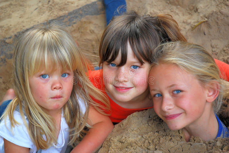 Sandpit friends. Portrait of three little Caucasian girls playing in the sandpit outdoors royalty free stock images
