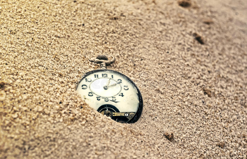 Sands of time. Antique pocket watch with cracked glass, partially buried in sand royalty free stock images