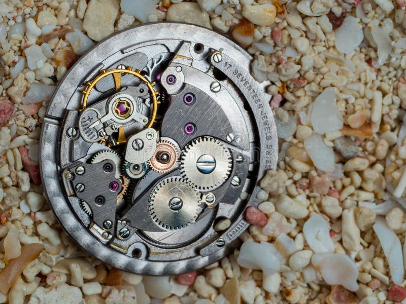 Sands of time, watch movement gears in pink coral sand royalty free stock image