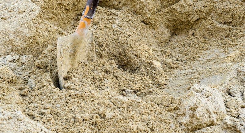 Sandschaufel und -stapel sandig in der Baustelle mit Kopienraum lizenzfreie stockfotografie