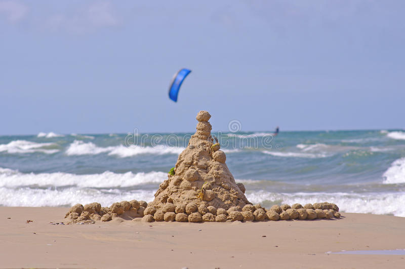Sandschloß und -Surfer im Meer stockfoto