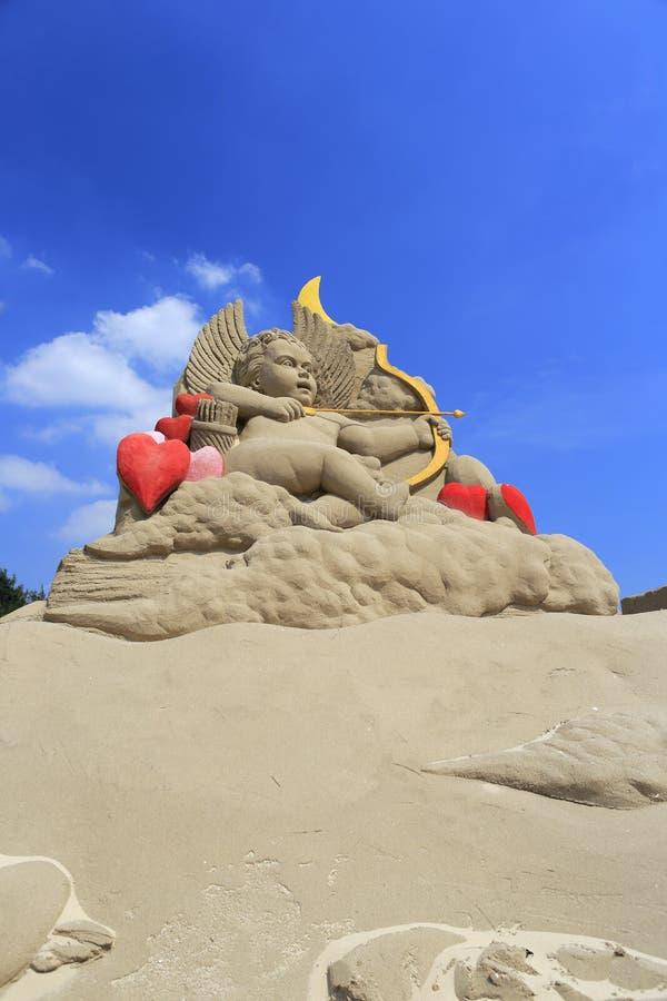 Sandskulptur av kupidonet arkivfoto