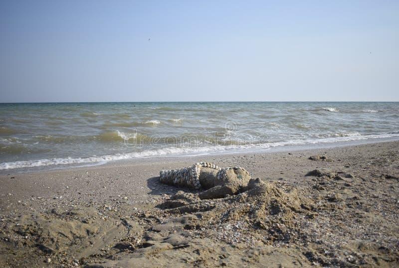 Sandskulptur einer Meerjungfrau mit Muscheln am Strand stockfotos