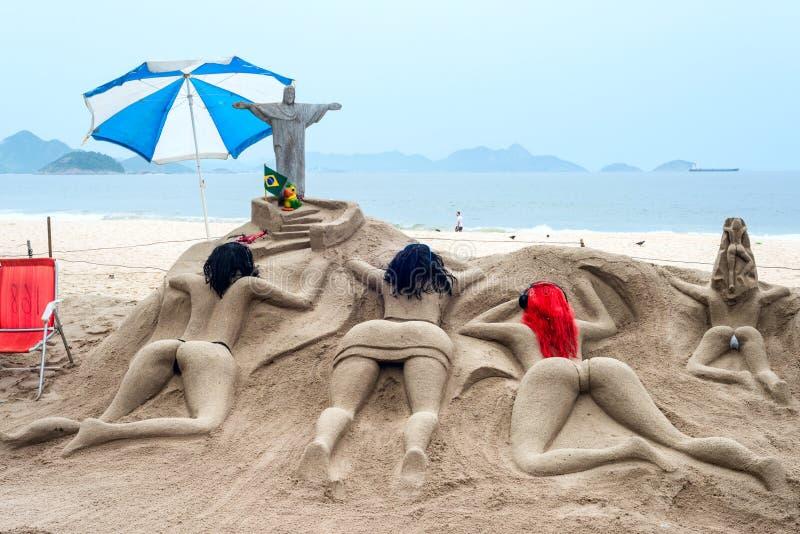 Sandskulptur solbadar på stranden av Copacabana royaltyfri fotografi
