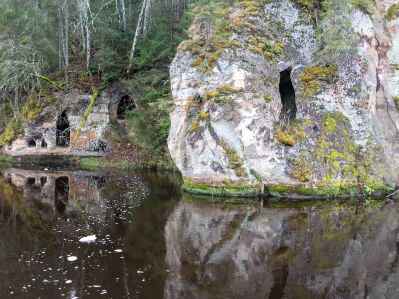 Sandsteinfelsen mit Höhlen reflektieren sich im dunklen Wasser stockfotografie