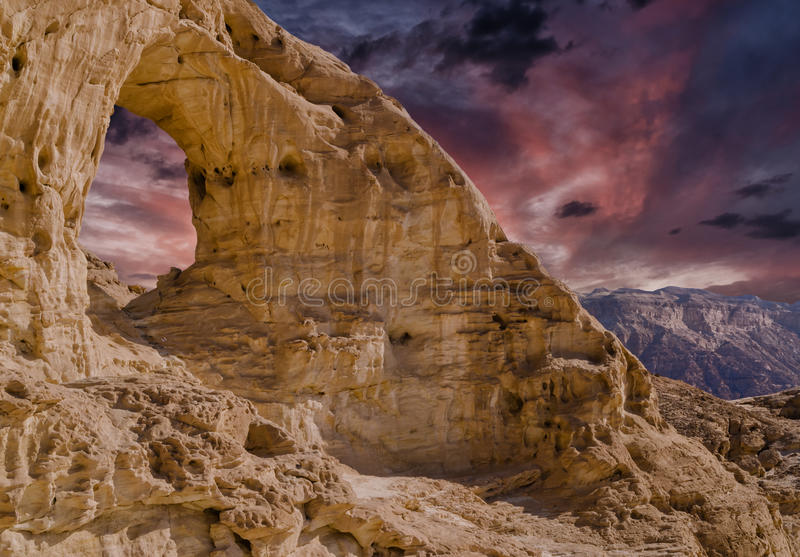 Sandstone arch at sunset in geological Timna park. This composite digital picture was done using my own photos I did in Timna park and Eilat - famous resort city royalty free stock images