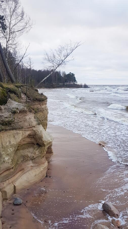 Sandstone cliffs and caves at the latvian coast line. Flooded beach. Sandstone cliffs at the Baltic sea shore. Sandstone cliffs and caves at the latvian coast royalty free stock photo