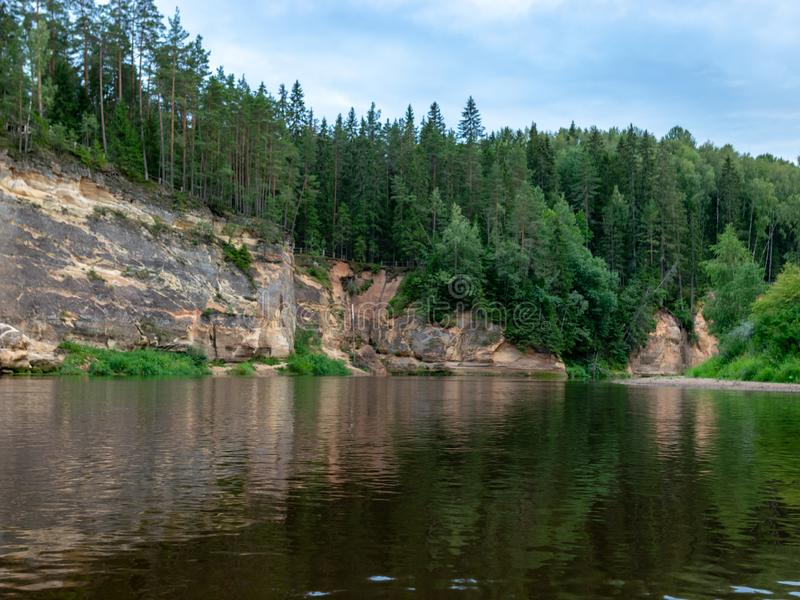 Sandstone cliffs in the evening light. Cliff and tree reflections, Ergļu cliffs, Latvia stock image