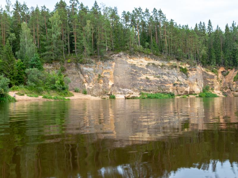 Sandstone cliffs in the evening light. Cliff and tree reflections, Ergļu cliffs, Latvia royalty free stock photography