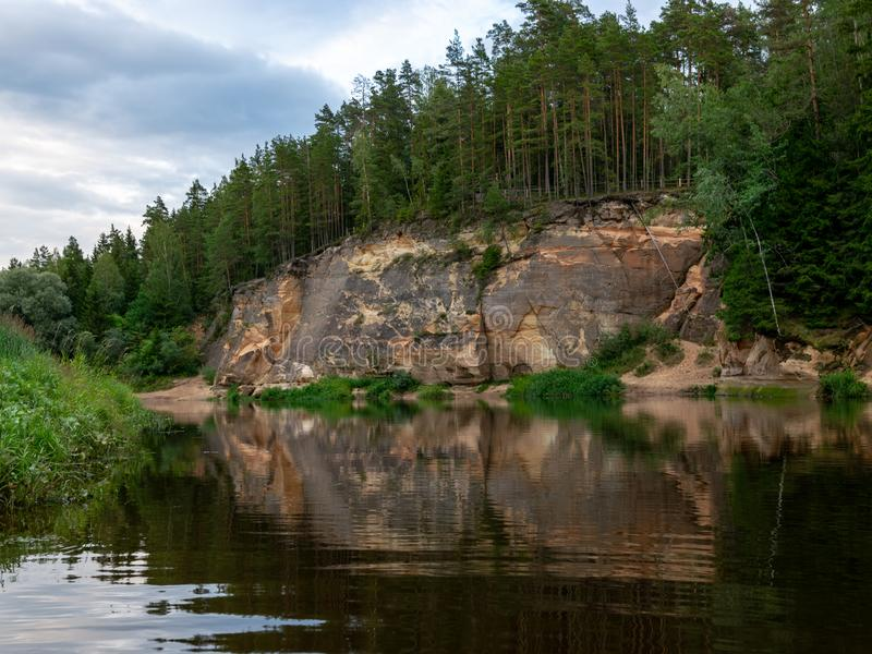 Sandstone cliffs in the evening light. Cliff and tree reflections, Erglu cliffs, Latvia royalty free stock photo