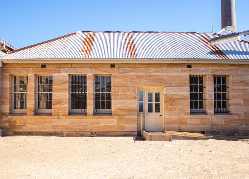 Sandstone convict brick building with corrugated iron roof, large tall windows, security grill, pebble courtyard against clear blu stock photos